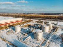 Staal of metaalopslagtanks voor olie of brandstof dichtbij de industriële pakhuis of fabrieksbouw in de winter, satellietbeeld stock afbeelding