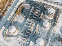 Staal of metaalopslagtanks voor olie of brandstof dichtbij de industriële pakhuis of fabrieksbouw in de winter, satellietbeeld stock foto's