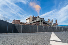 Staalfabriek met barbwireomheining die rode wolk produceren Royalty-vrije Stock Fotografie