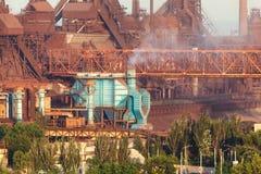 Staalfabriek met schoorstenen bij zonsondergang Stock Foto's