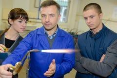 Staalfabriekenleraar die studenten tonen hoe te om gaslasser veilig te gebruiken royalty-vrije stock afbeeldingen