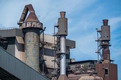 Staalfabriekschoorstenen en blauwe sluw Royalty-vrije Stock Foto's