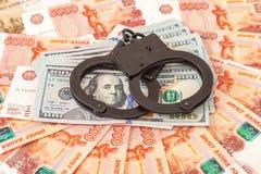 Staalhandcuffs die op een stapel dollarrekeningen liggen Stock Foto's