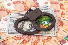 Staalhandcuffs die op een stapel van dollarrekeningen en creditcard liggen Royalty-vrije Stock Foto