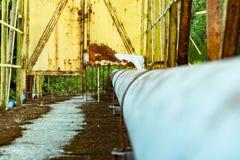 Staalpijpen in de oliefabriek, oude roestige pijpen die de weg kruisen royalty-vrije stock fotografie