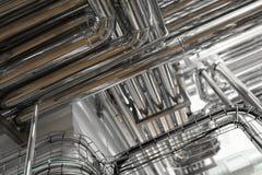 Staalpijpleidingen en kabels in fabrieksbinnenland als farmaceutisch de industrieconcept als achtergrond royalty-vrije stock afbeeldingen