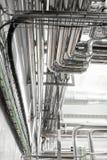Staalpijpleidingen en kabels in fabrieksbinnenland als farmaceutisch de industrieconcept als achtergrond stock foto's