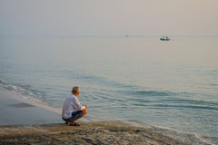 Staart de zonsopgang bejaarde Thaise mens uit aan overzees bij de kleine vissersboot stock foto's