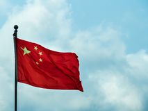 Staatsflagge des des Peopes die Republik- Chinafliegens am vollen Mast gegen einen hellblauen Himmel lizenzfreie stockbilder