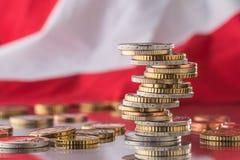 Staatsflagge von Österreich und von Euromünzen - Konzept Stapel der Euromünzen e Lizenzfreies Stockbild