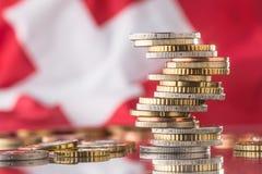 Staatsflagge von der Schweiz und von Euromünzen - Konzept Euro zerrissen zur Hälfte gegen alten Hintergrund Stockbilder