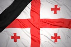 Staatsflagge von Georgia mit schwarzem Trauerband Stockbilder