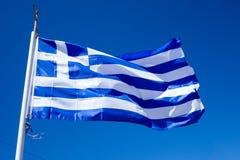 Staatsflagge von Griechenland gegen Hintergrund des blauen Himmels Stockbild