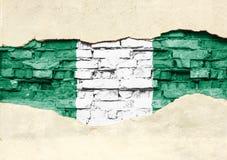 Staatsflagge von Nigeria auf einem Ziegelsteinhintergrund Backsteinmauer mit teilweise zerstörtem Gips, Hintergrund oder Beschaff stockbilder