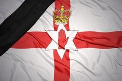 Staatsflagge von Nordirland mit schwarzem Trauerband Stockfotografie