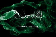Staatsflagge von Saudi-Arabien machte vom farbigen Rauche, der auf schwarzem Hintergrund lokalisiert wurde Abstrakter seidiger We lizenzfreie stockbilder