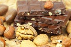 Stab der Schokolade und der Muttern auf einer Weidenmatte Lizenzfreies Stockbild