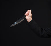 Stabbing. Closeup view of a hand holding a large kitchen knife in a stabbing motion Stock Photo
