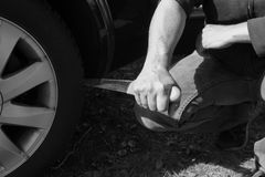 Stabbing a car tire with a long knife Stock Photos