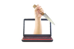 Stabbing hand with knife coming out of computer monitor Royalty Free Stock Photo
