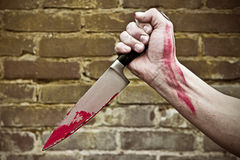 Stabbing knife. Fist, holding a blood stained knife, stabbing Royalty Free Stock Photography