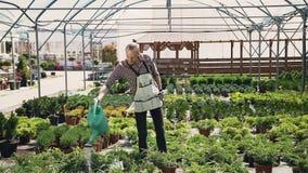 Stabile Kamerabewegung Ein Junge mit einem Bart in einem Gartenschutzblech gießt Zierpflanzen mit Wasser Garten mit Blumen an stock video footage