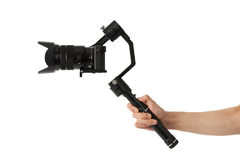 Stabilization System with 3-axis gimbals & Mirrorless Camera. 3-axis gimbals Stabilization System with Mirrorless Camera. Using this equipment, a Videographer Stock Photography