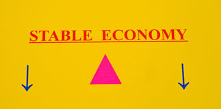 A stable economy. A simple abstract image of the stable economy balanced on a fulcrum and not tipping to left or right. The background is plain yellow parchment Royalty Free Stock Photography