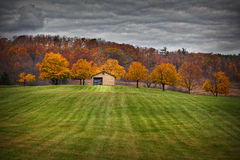 Stable in fall. Stable with colorful trees and black clouds in fall Stock Photography