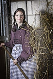 Stable girl. Pretty young girl working in the stable tossing the hay Stock Photography