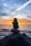 Stable vertical cairn at sunset on the sea Royalty Free Stock Photos