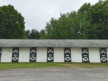 Stables at a horse track with trees and dirt road. Stables at a horse track with trees, dirt road and green doors Stock Photography