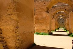 Stables in Meknes in morocco. Arches in morrocan horse stables in Meknes, morocco. Ancient Stables of Meknes. Horses, ruins. with sunshine shadows and shade stock photo