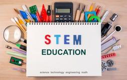 STACCHI il testo dal gambo di istruzione sul taccuino sopra i rifornimenti di scuola o l'ufficio s Immagini Stock