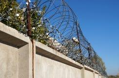 Stacheldraht auf einem konkreten Zaun Lizenzfreie Stockfotos