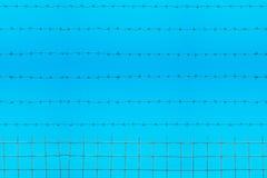 Stacheldraht auf Hintergrund des blauen Himmels Stockfotos