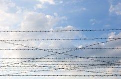 Stacheldraht gegen den Hintergrund des bewölkten Himmels Lizenzfreie Stockfotografie