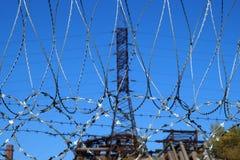 Stacheldraht gegen einen Mast von Stromleitungen Stockfotos
