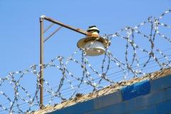 Stacheldraht und Lampe gegen den blauen Himmel Lizenzfreie Stockfotos