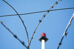 Stacheldraht und Notbeleuchtung gegen den blauen Himmel, vorgewähltes f Lizenzfreie Stockfotografie