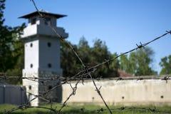 Stacheldraht und unscharfer Wachturm im Hintergrund im Konzentrationslager stockbilder