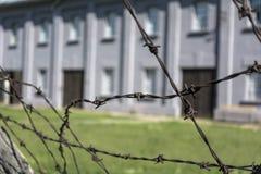 Stacheldraht und unscharfes Gebäude im Konzentrationslager lizenzfreie stockfotos