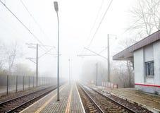 Stacja kolejowa na mgłowym dniu Obrazy Royalty Free
