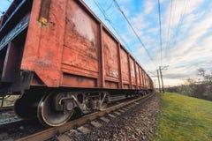 Stacja kolejowa z ładunku pociągiem przy zmierzchem i furgonami Fotografia Stock