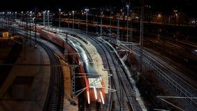 Stacja kolejowa z ruchu pociągiem przy nocą Fotografia Royalty Free