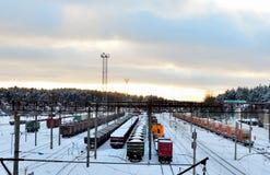 Stacja kolejowa z wiele sposobami dokąd tam są wiele pociągi z samochodami, spłuczkami i zbiornikami, zdjęcie royalty free