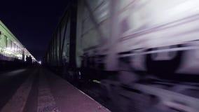 Stacji kolejowej platforma z ludźmi na nim i łańcuchu poruszający furgony zbiory
