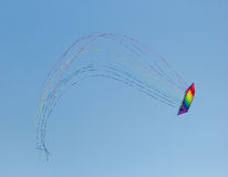 Stack of 12 stunt kites. In rainbow colours on a blue sky background. The long tails form a half circle Stock Photos