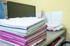 Stack of accounting documents with computer screen on desk royalty free stock images