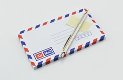Stack of air mail envelopes with pen and stamp on white. Background royalty free stock images